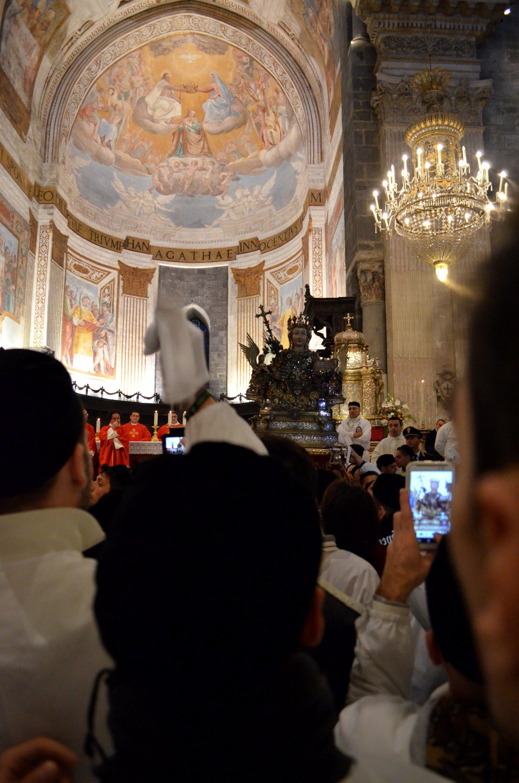 La processione inizia dentro la cattedrale di Catania. I devoti stano uscendo con il busto reliquiario